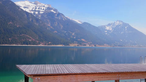 Wooden quay beside magnificent Achensee lake, Austria. Spectacular winter pan Footage