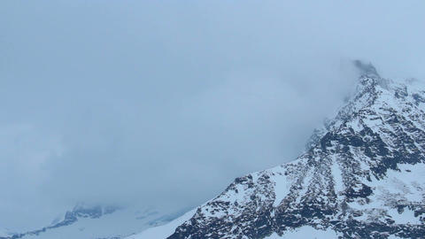 Snowy mountain peak hidden in thick clouds, weather forecast, storm warning Live Action