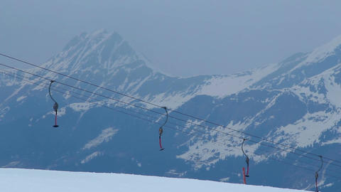Empty cableway on windy snowy mountain range, storm warning, avalanche hazard Footage