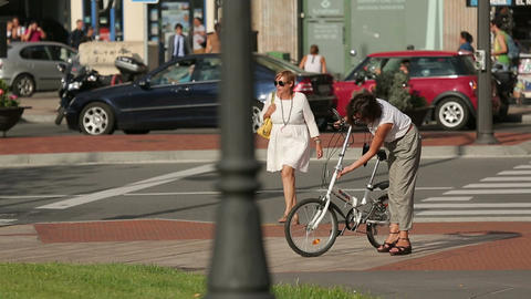 Busy street traffic, active urban life, woman crossing road, lady fixing bicycle Footage