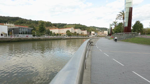 People walking clean river embankment in European city, place for recreation Footage