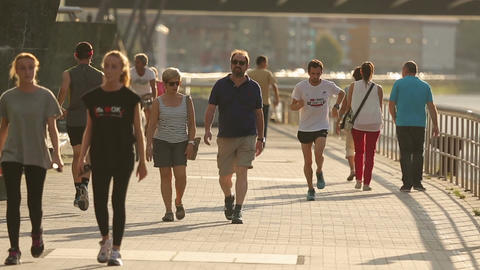 Men and women strolling and jogging along river embankment, morning in the city Footage