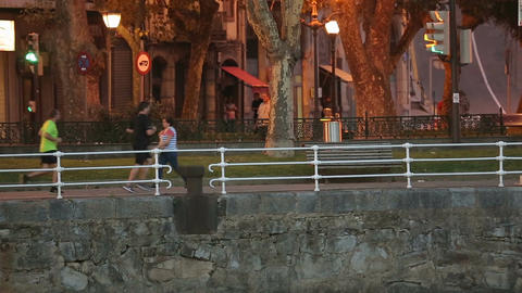 Quiet European street in the evening, people strolling and running on walkway Footage