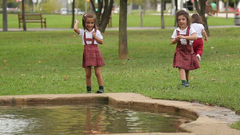 Little children playing, throwing stones into water at the park. Happy childhood Live Action