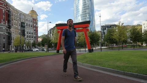 Handsome tourist strolling around modern European city, enjoying sightseeing Footage