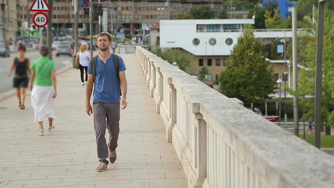 Young male with backpack walking across the bridge, looking at city landmarks Footage