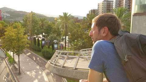 Male tourist enjoying amazing balcony view in resort city, happy guy on vacation Footage