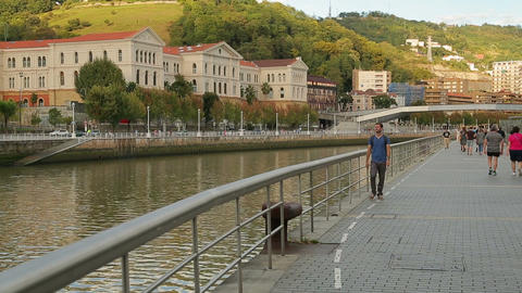 Male backpacker walking along the city riverside, stops to look down at water Footage