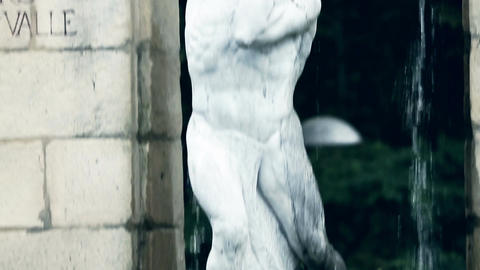 Detailed view of old marble sculpture of a man and two human faces beneath him Footage