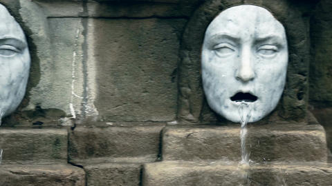 Horizontal pan of two marble fountain sculptures with horrifying grotesque faces Footage