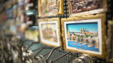 Zoom-in on Prague Czech Republic souvenir fridge magnet displayed at gift shop Footage