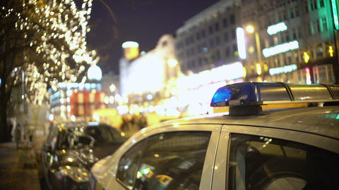 Police car at mass protest site, officer patrolling crowded city street at night Footage