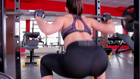 Sexy female athlete wearing tight leggings doing squats with barbell in the gym Footage