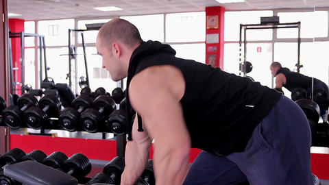 Professional male bodybuilder exercising with heavy dumbbells before competition Footage