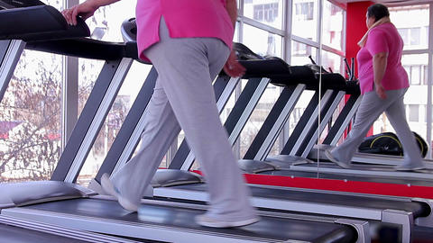Tired overweight woman sweating on treadmill after intensive workout in the gym Footage