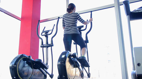 Active housewife exercising on elliptical cross trainer in the gym, body care Live Action