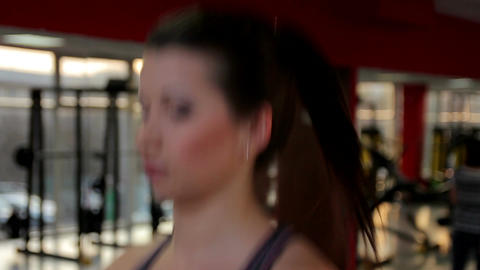 Hot brunette taking care of her fit body, exercising on treadmill in the gym Live Action