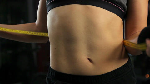 Fit lady with flat belly measuring waist after intensive workout, weight loss Footage