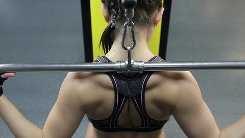 Back view of strong fit female athlete finishing pulldown exercise in the gym Footage
