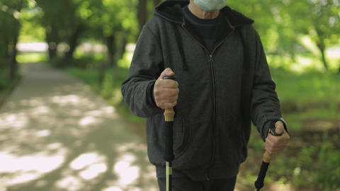 Active senior old man training Nordic walking with ski trekking poles in park Live Action
