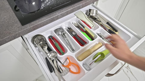 Male hand opens kitchen drawer, takes and examine some objects inside Live Action
