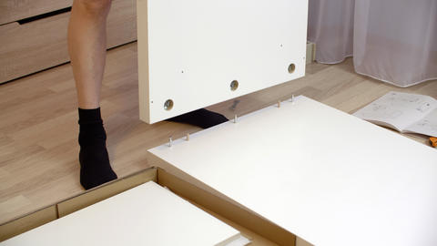 Man assembling new furniture for bed room on floor. Handyman collecting white Live Action