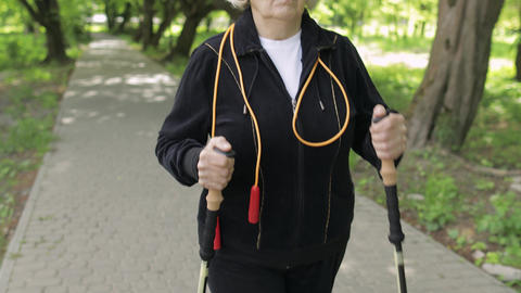 Active senior old woman training Nordic walking with ski trekking poles in park Live Action