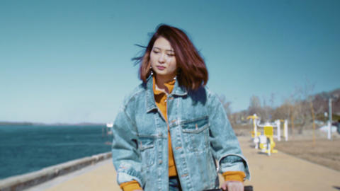 Young asian woman in a jeans jacket rides the scooter near the river Live Action