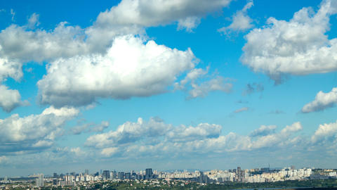 White clouds flowing in blue sky on sunny summer day. Clouds flowing over buildings. 4k timelapse Live Action