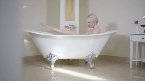 Wide shot of woman shaving legs in bathtub. Side view portrait of confident Live Action