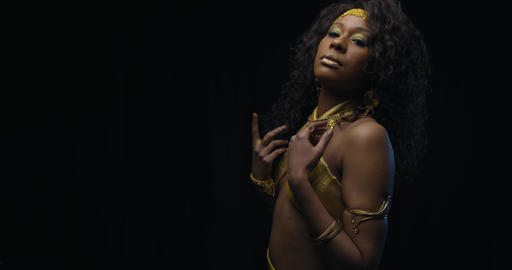 Gorgeous black woman is posing in gold dress and jewelry, black background, 4k Live Action