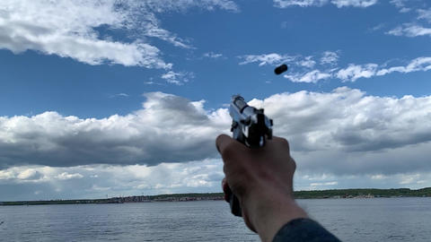 Mans hand with automatic gun pistol close-up. Shooting to blue sky Live Action