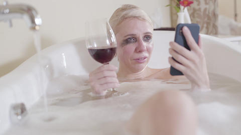 Crying blond woman reading messages on smartphone and drinking red wine Live Action