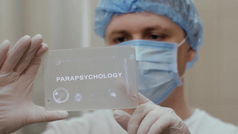 Doctor uses tablet with text Parapsychology Live Action