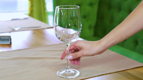 The waitress puts a glass glass glass, a knife and a fork on the table. In the background, a window Live Action