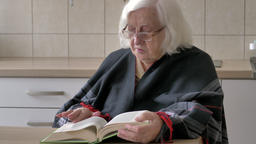 Old woman is reading book. Face expression Live Action