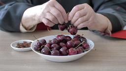 Old woman is eating sweet cherries from a plate Live Action
