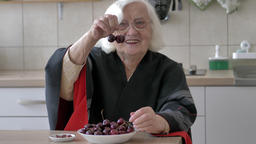 Funny, happy old woman is picking sweet cherries from a plate Live Action