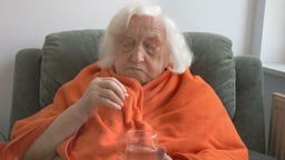 Old, ill lady is taking medicine and coughing Live Action