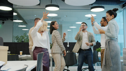 Slow motion of cheerful coworkers dancing in shared office having fun together Live Action