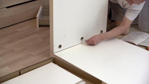 Man assembling furniture at home Live Action