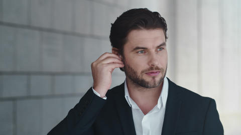 Businessman talking by wireless earphones in city. Employee using earbuds Live Action
