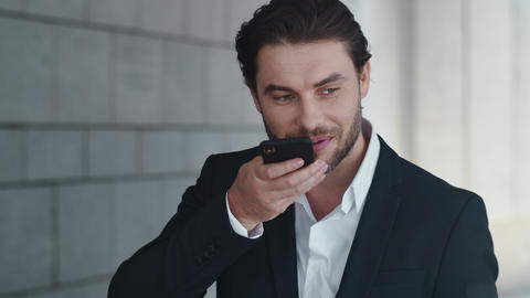 Happy business man recording voice message on cellphone outside Live Action