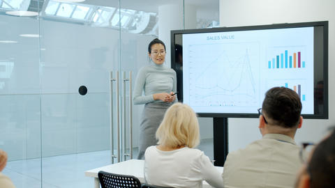 Cheerful Asian girl speaking about marketing research in conference room Live Action
