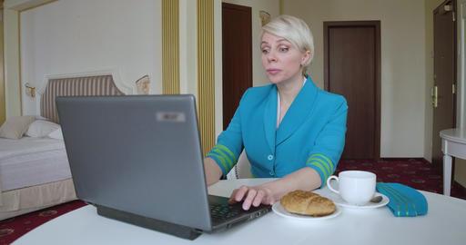 Cheerful blond woman in stewardess uniform sending message online using laptop ライブ動画