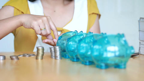 Hands of woman putting money coin into 4 clear piggy bank with blank metaphor separate kind of money Live Action