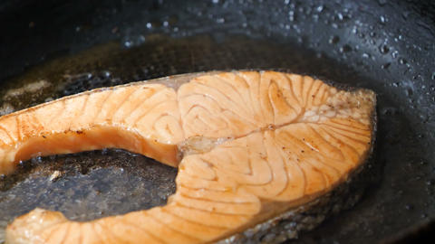 People using a wooden spatula to grilling a piece of slice salmon steak, preparing and cooking the GIF