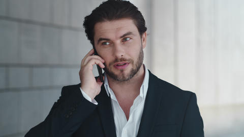 Businessman having phone conversation at street. Manager talking on smartphone Live Action