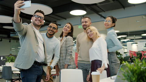 Multi-racial group of coworkers taking selfie in office room using smartphone Live Action