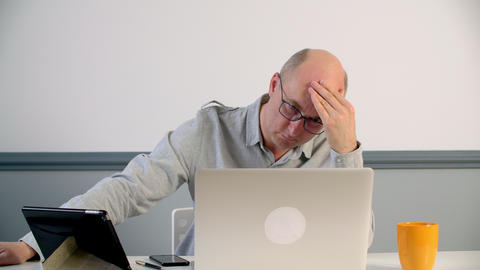 Depressed man touching forehead while hard work on laptop in office. Tired man GIF
